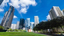 Fort Bonifacio skyline. Verdant green fields of an empty lot in front. Modern office buildings and condos in back.