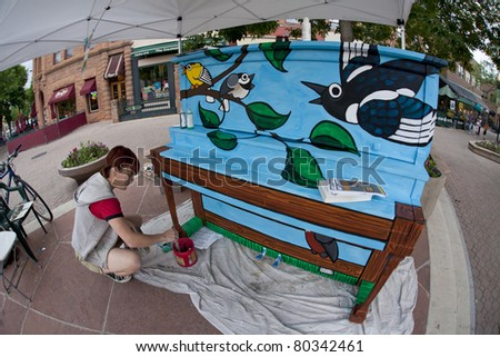 FORT COLLINS, CO. - JUNE 19: A fish eye perspective of artist Ren Burke paints mural on the piano at Old Town square as part of Pianos About Town public art program June 19, 2011 in Fort Collins, CO.