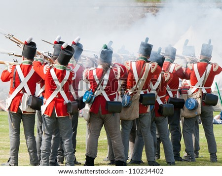"""FORT GEORGE, SCOTLAND- AUGUST 11 : Redcoat soldiers firing rifles during the annual """"Celebration of the Centuries"""" event at Fort George, Scotland, August 11, 2012"""