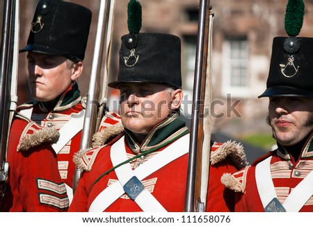 """FORT GEORGE, SCOTLAND- AUGUST 11 : Redcoat soldiers marching during the annual """"Celebration of the Centuries"""" event at Fort George, Scotland, August 11, 2012"""