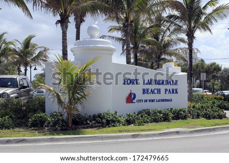 FORT LAUDERDALE, FLORIDA - APRIL 6, 2013: Closeup of Ft Lauderdale Beach Park sign with palm trees and autos in the background. Location is at 1100 Seabreeze Boulevard and is open 5 AM to midnight.