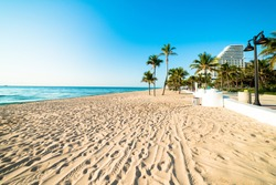 Fort Lauderdale  South Florida beach with no one on it on beautiful blue sky morning with hotels in background