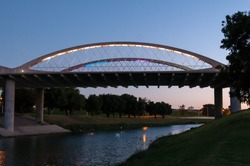 Fort Worth West 7th street bridge. Trinity River flowing under the bridge during sunset. Reflections on the water and Trinity Park in the background.