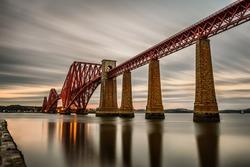 Forth Railway Bridge over the Firth of Forth at sunset in Edinburgh, Scotland, United Kingdom. Long exposure.