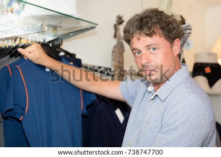 forties man in shopping store try to buy clothes #738747700