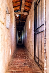 Fortress tunnel empty path passage with gate door in Castiglione del Lago in Italy with windows and shadows in historic town village fort