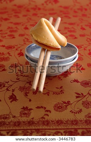 fortune cookie and chopsticks on red/gold silk