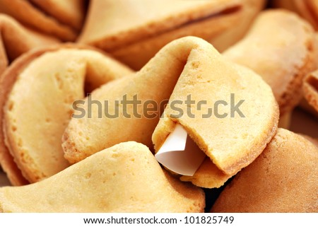 Fortune cookie background.  Macro with shallow dof.  Selective focus on edge of opened cookie with paper strip.
