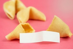Fortune Cookie on a crimson background. Close-up of foreboding broken asian cookies with white piece of paper with copy space on a dark pink background
