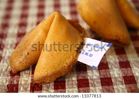 Fortune cookie on a red and white checkered background.