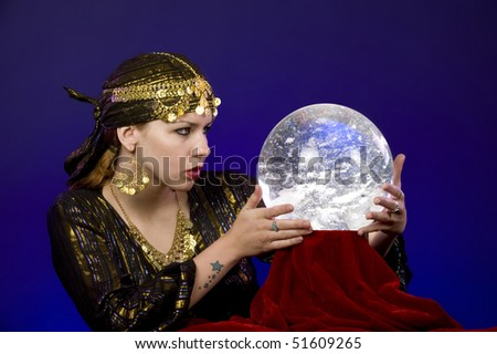 Fortune-teller divines with crystal ball.