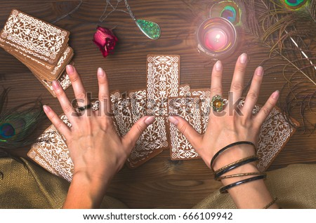 Fortune teller female hands and tarot cards on wooden table. Fortune teller. #666109942