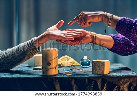 Fortune teller woman reading palm lines around candles and other magical accessories. Witch during fortune telling, palmistry and divination. Magic ritual  Stock foto ©