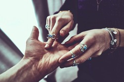 Fortune teller woman wearing silver rings with turquoise stone and bracelets reads palm lines during fortune telling and prediction the future. Palmistry and occult divination