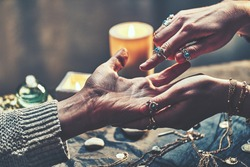 Fortune teller woman wearing turquoise silver rings and bracelets reads palm lines during fortune telling to prediction the future around candles and magic accessories. Palmistry and divination