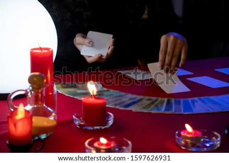 Fortune Teller young Asian woman Gypsy glowing crystal ball, tarot cards, magic, and composition esoteric astrology object to predict destiny or future. superstition and supernatural phenomenon