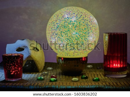 Fortune telling,a illuminated crystal ball on a table with some candles,some glass stones and a mask,there is also a gradient background.