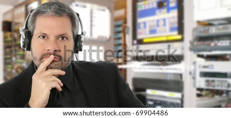 Forty something attractive man in television studio listening to audio on headset.