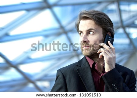 Forty years old businessman standing inside modern office building talking on a mobile phone