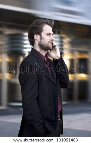 Forty years old businessman standing outside modern office building talking on a mobile phone