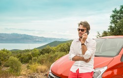Forty years old caucasian man (driver, tourist or businessman) talking on a mobile phone (smartphone) in front of a car. Landscape (mountain, sea) as background. Holiday (vacation) road trip concept.