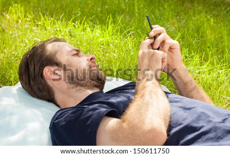 Forty years old caucasian man looking at mobile phone while laying on grass in park during a sunny summer day