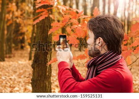 Forty years old caucasian man taking autumn outdoor photo with mobile phone - enjoying nature and modern technology