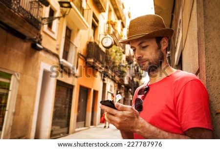 Forty years old caucasian tourist man looking at mobile phone outdoor near old city buildings - summer holiday