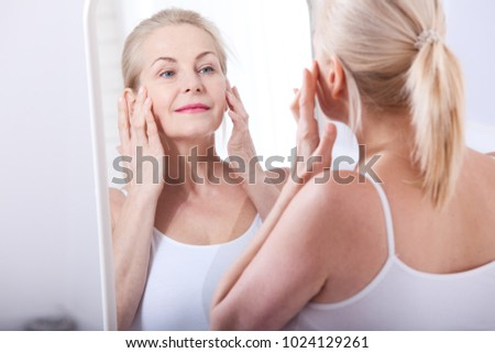 Forty years old woman looking at wrinkles in mirror. Plastic surgery and collagen injections. Makeup. Macro face. Selective focus on the face. Realistic images with their own imperfections.