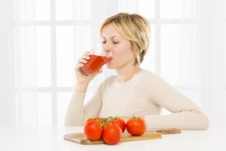 Forty years woman drinking tomato juice