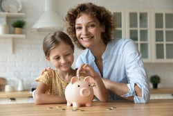 Forward looking parent. Portrait of happy smiling mom cuddling small school age girl putting coin to piggybank. Caring single mother try to secure daughter future saving money on bank deposit account
