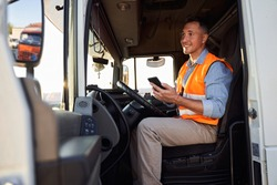 Forwarder or truck driver in drivers cap holding mobile phone