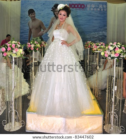 FOSHAN, CHINA–AUG 20: A model walks the runway at the Fall Wedding Expo 2011 at FoShan Stadium on August 20, 2011 in FoShan, China. More than 100 wedding photography, production planning companies took part.