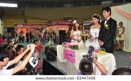 FOSHAN, CHINA–AUG 20: Models pose for photos at the Fall Wedding Expo 2011 at FoShan Stadium on August 20, 2011 in FoShan, China. More than 100 wedding photography, production planning companies took part.