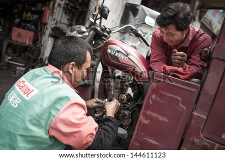 FOSHAN, GUANGDONG/CHINA - MARCH 16: Unidentified garage mechanic works on motorcycle as customer watches in Shunde District of Foshan City, Guangdong Province, China on March 16th, 2013.