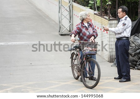 FOSHAN, GUANGDONG/CHINA - MARCH 16: Unidentified security policeman talks to unidentified cyclist in Shunde District of Foshan City, Guangdong Province, China on March 16th, 2013.