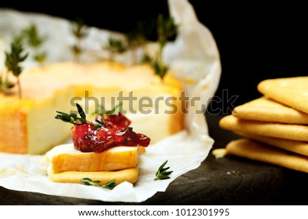 Foto still life delicious brie cheese or  orange camembert in paper with mouth-watering snacks and crackers with brie cheese, raspberry jam and thyme on a black background