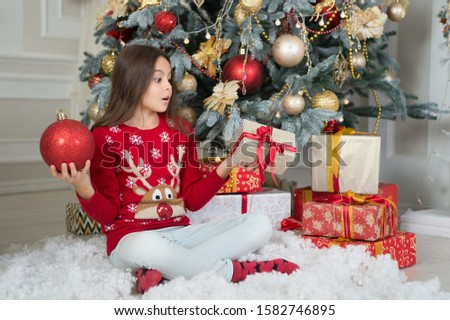 Found gift surprise under christmas tree. Surprised child hold gift box and ball. Christmas surprise. Small girl keep mouth opened of surprise. Surprise inside the box. Boxing day. New year.