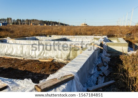 Foundation construction for a house in a cottage village. Film covered foundation. Autumn, sunny Stock photo ©