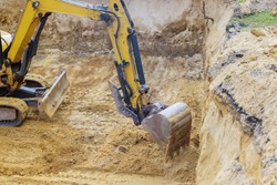 Foundation construction in excavator at earthworks on backhoe loader digs of underground