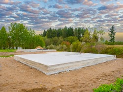 Foundation in a suburban area. Poured foundation next to taiga. Concept - building a house. Foundation as a symbol of erected house. Construction of a country house. Building bussiness