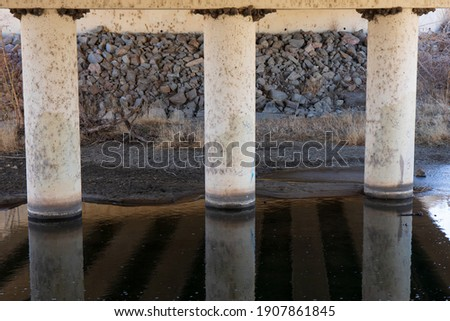 Foundational pillars under a bridge.  White pylons reflected in water with.a rock and concrete background.  Bird nests line the top of the pillars.   Photo stock ©