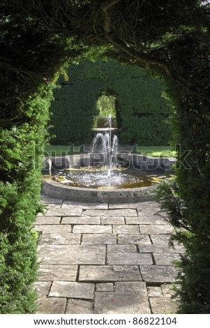 Fountain and pond enclosed by Yew hedging in an English country garden.