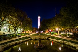 Fountain and the Washington Monument at night in Mount Vernon, Baltimore, Maryland.