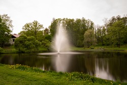 Fountain in a pond in the city, surrounded by trees and grass, chill