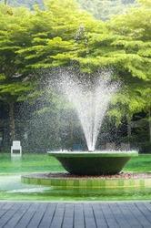 Fountain in fresh summer green pool.