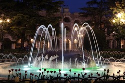 Fountain in front of the ancient roman amphitheatre in Verona, Italy at night