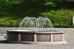 Fountain in the city square. View of the fountain against a background of green grass.