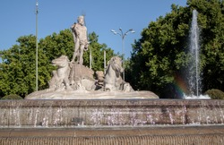 Fountain of Neptune in the old town of Madrid, Spain. The statues shows the god of the sea, with a trident in one hand and a coiled snake in the other, surrounded by dolphins and two sea horses.
