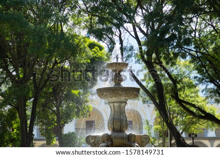 Fountain of the sirens in Antigua Guatemala- fountain in the middle of a park surrounded by trees in colonial city